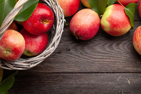 Ripe garden apple fruits in basket on wooden table. Top view flat lay with copy space 免版税图像