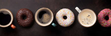 Coffee cups and colorful donuts on stone table. Top view flat lay