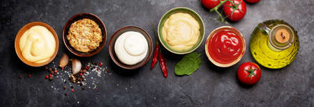 Set of various sauces. Popular sauces in bowls - ketchup, mustard, mayonnaise on dark stone table. Top view flat lay