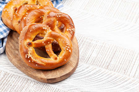 Fresh baked homemade pretzel with sea salt on wooden table. Classic beer snack. With copy space Foto de archivo