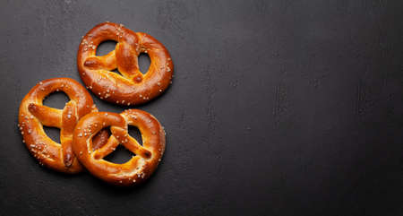 Fresh baked homemade pretzel with sea salt on stone table. Classic beer snack. Top view flat lay with copy space Banco de Imagens