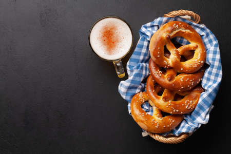 Lager beer mug and fresh baked homemade pretzel with sea salt on stone table. Classic beer snack. Top view flat lay with copy space Banque d'images