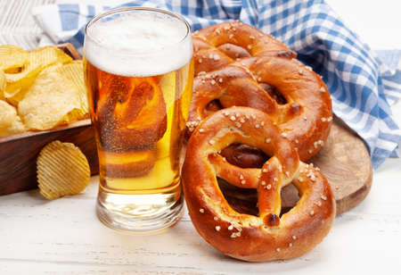 Lager beer mug, potato chips and fresh baked homemade pretzel with sea salt on wooden table. Classic beer snack