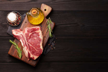 Raw T-bone beef steak on cutting board. Top view flat lay with copy space Banque d'images