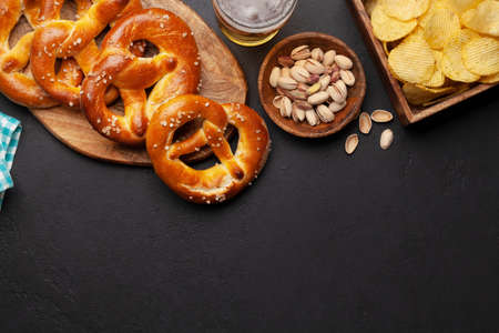 Lager beer mug, nuts, potato chips and fresh baked homemade pretzel with sea salt on stone table. Classic beer snack. Top view flat lay with copy space