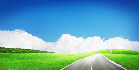 Green grass field, asphalt road and sunny sky with clouds over horizon. Wide summer landscape