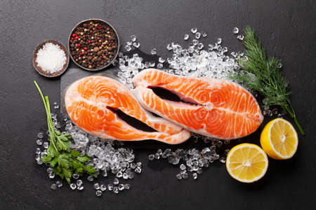 Fresh raw salmon cooking. Fish steaks with herbs and spices. Top view flat lay