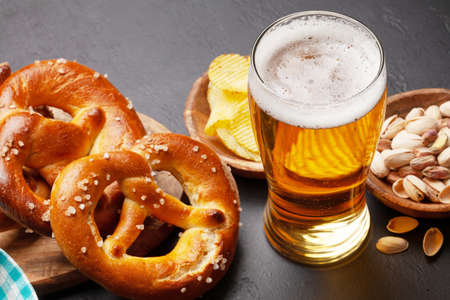 Lager beer mug, nuts, potato chips and fresh baked homemade pretzel with sea salt on stone table. Classic beer snack Banque d'images