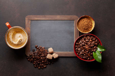 Roasted coffee beans, ground powder and cup of hot espresso coffee. Top view flat lay with chalkboard for copy space