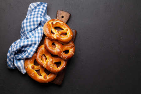 Fresh baked homemade pretzel with sea salt on stone table. Classic beer snack. Top view flat lay with copy space Banque d'images