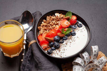 Healthy breakfast with bowl of granola, yogurt and fresh berries. Fitness protein meal