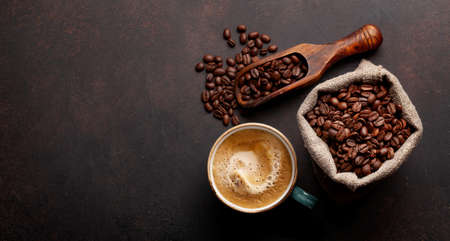 Roasted coffee beans and cup of hot espresso coffee. Top view flat lay with copy space