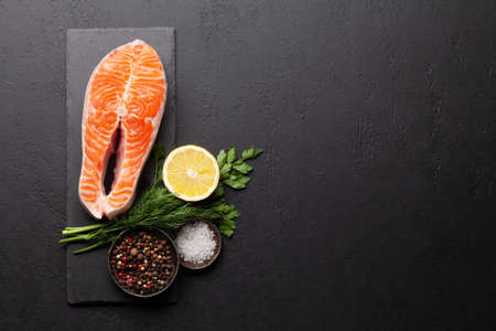 Fresh raw salmon cooking. Fish steak with herbs and spices. Top view flat lay with copy space
