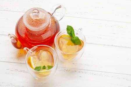 Herbal tea with mint and lemon. Tea cup and teapot on wooden table. With copy space