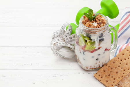 Healthy breakfast with jar of granola, yogurt and fresh berries. Fitness protein meal. Dumbbells and tape measure. Diet concept. With copy space