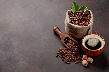 Roasted coffee beans, brown sugar and cup of hot espresso coffee. With copy space