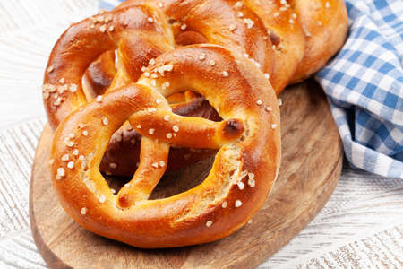 Fresh baked homemade pretzel with sea salt on wooden table. Classic beer snack Banque d'images