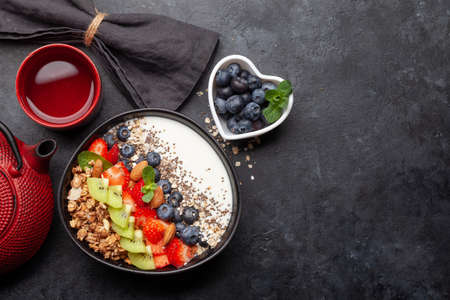 Healthy breakfast with bowl of granola, yogurt and fresh berries and herbal tea. Fitness protein meal. Top view flat lay with copy space