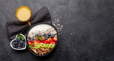 Healthy breakfast with bowl of granola, yogurt and fresh berries. Fitness protein meal. Top view flat lay with copy space Banque d'images