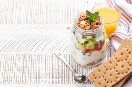 Healthy breakfast with jar of granola, yogurt and fresh berries. Fitness protein meal and diet concept. With copy space