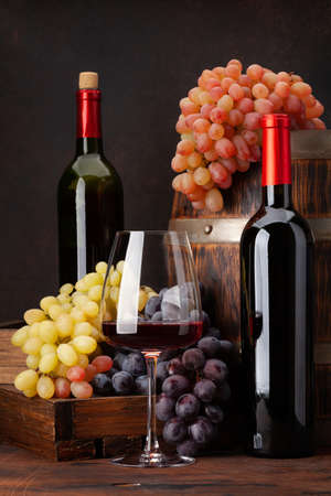 Wine bottles, grapes, glass of red wine and old wooden barrel