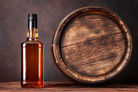 Scotch whiskey bottle and old wooden barrel. With copy space