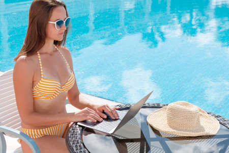 Young woman using laptop for remote work or education near a swimming pool. With copy space Banque d'images