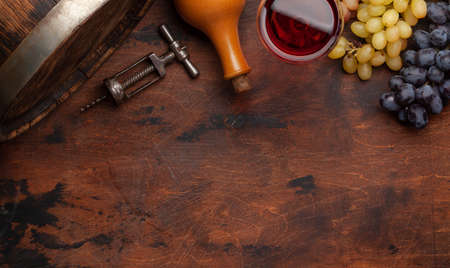 Wine bottle, grapes, glass of red wine and old wooden barrel. Top view flat lay with copy space