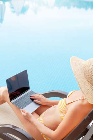 Young woman using laptop for remote work or education near a swimming pool. With copy space for your text or app Banque d'images