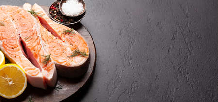 Fresh raw salmon cooking. Fish steaks with herbs and spices. With copy space
