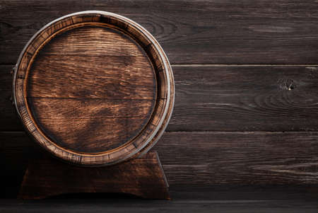 Old wooden barrel for wine or whiskey aging. In front of wooden wall with copy space Banque d'images