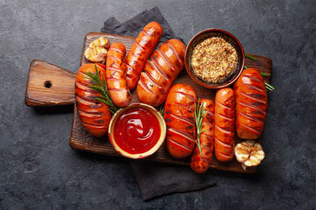 Hot grilled sausages on wooden board with ketchup and mustard. Top view flat lay