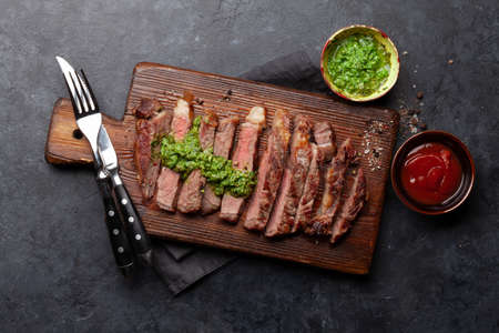 Sliced beef steak with sauce. On cutting board. Top view flat lay