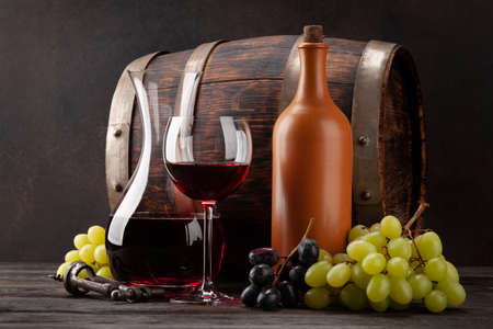 Wine bottle, decanter, glass of red wine, grapes and old wooden barrel