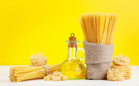 Various types of Italian pasta and olive oil in front of yellow background with copy space