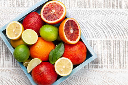 Various fresh citrus fruits in wooden box. Bood orange, lime, lemon. Top view flat lay with copy space