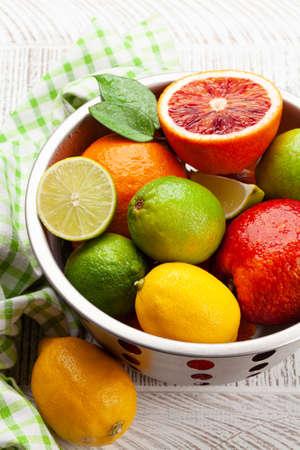 Various fresh citrus fruits in colander. Bood orange, lime, lemon
