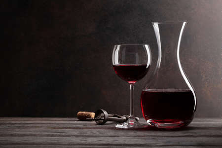Wine decanter, glass of red wine, corkscrew and corks. With copy space