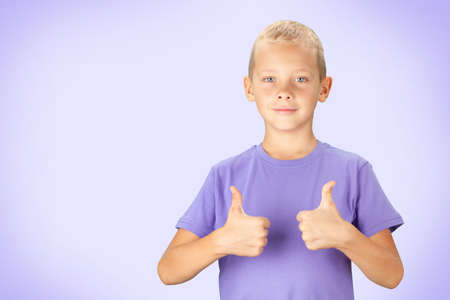 Funny boy showing thumbs up. Over purple background with copy space Banque d'images