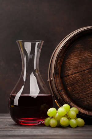 Wine decanter, grapes and old wooden barrel. With copy space