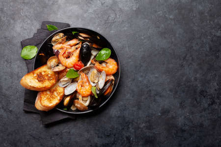 Mixed grilled seafood. Various roasted shrimps, mussels and shellfish in frying pan. Top view flat lay with copy space Foto de archivo