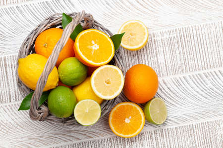 Fresh ripe citrus fruits basket on wooden table. Top view flat lay with copy space