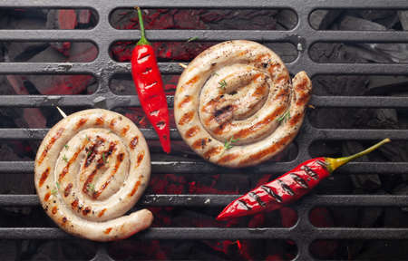 Hot spicy grilled sausages on coal grill. Top view flat lay Standard-Bild