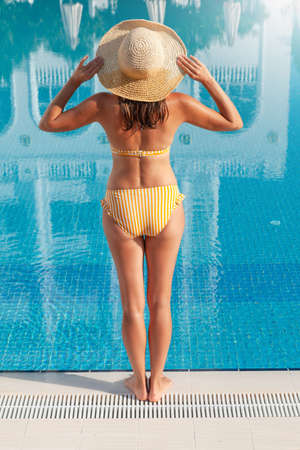 Woman relaxing in swimming pool on summer vacation. Hot sunny holiday concept Standard-Bild