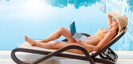 Young woman using laptop for remote work or education near a swimming pool. With copy space for your text or app Standard-Bild