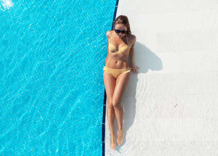 Woman relaxing in swimming pool on summer vacation. Hot sunny holiday concept. Top view flat lay with copy space