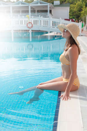 Woman relaxing in swimming pool on summer vacation. Hot sunny holiday concept with copy space