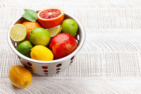 Various fresh citrus fruits in colander. Bood orange, lime, lemon. With copy space