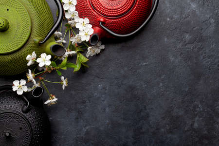 Japanese tea in tea pot and cherry blossom on stone table. Top view flat lay with copy space