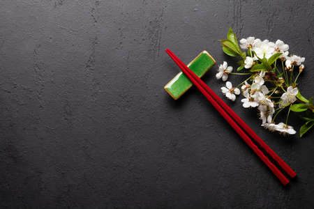 Japanese food background with cherry blossom and sushi chopsticks. Top view flat lay with stone board for your food or text